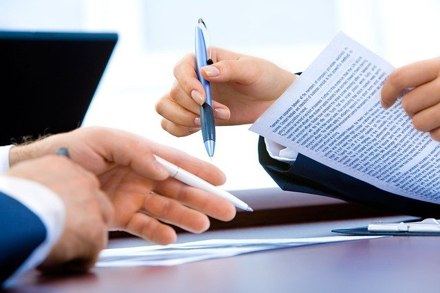 man and woman holding contracts sat at desk, focus on hands, faces out of shot