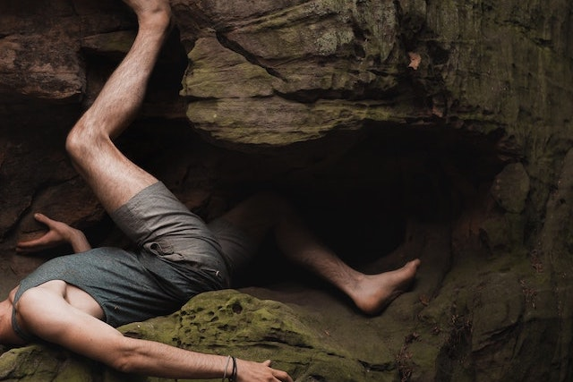 man lying on cliff rocks