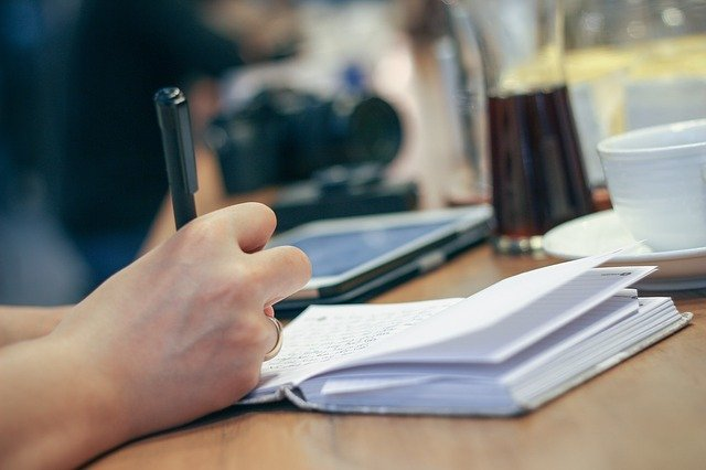 woman writing in a notebook, focus on hands
