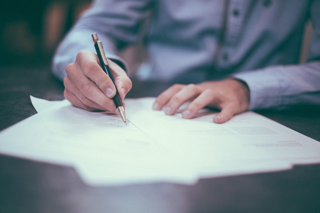 man writing by hand on a piece of paper. Paper in foreground with man in background.