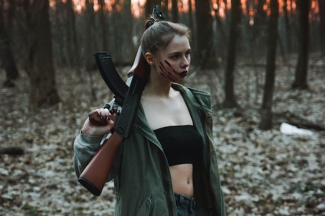 woman in woods with AK-47