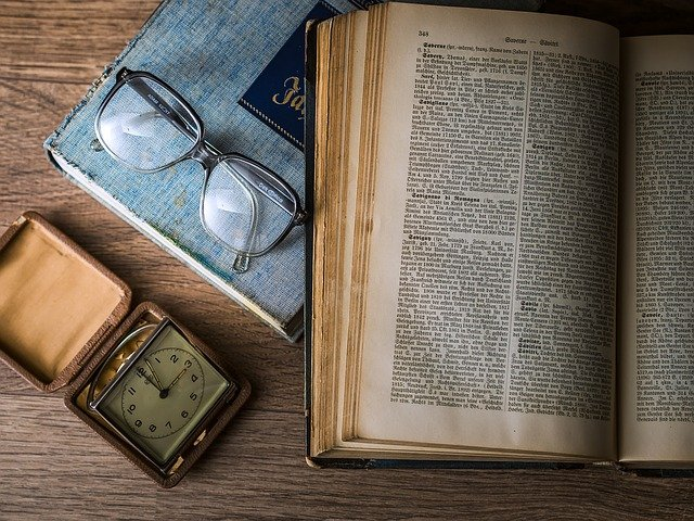 a dictionary, small carry clock and a pair of glasses on a wooden desk