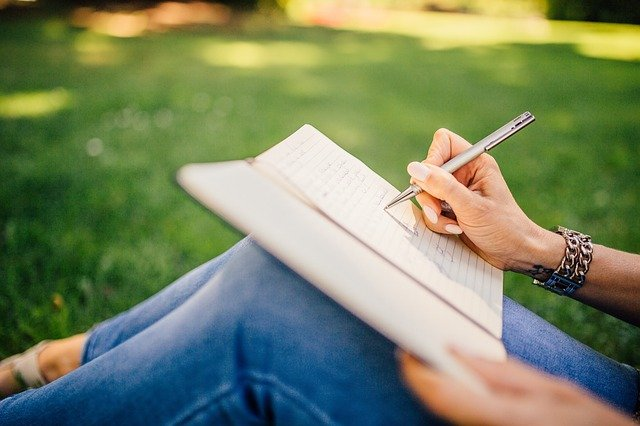 woman sat on grass, writing in a notebook