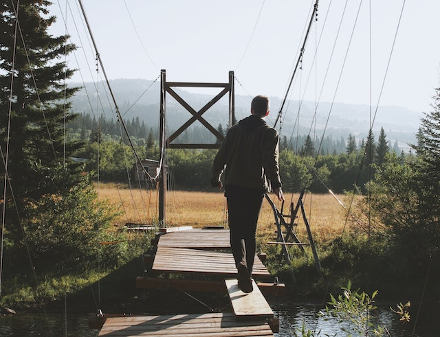 man walking on a board between to sections of wooden bridge