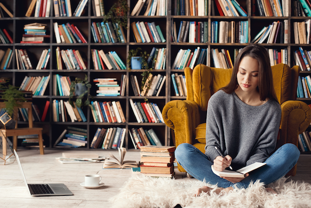 a woman sat on the floor writing in a notebook in front of some bookshelves