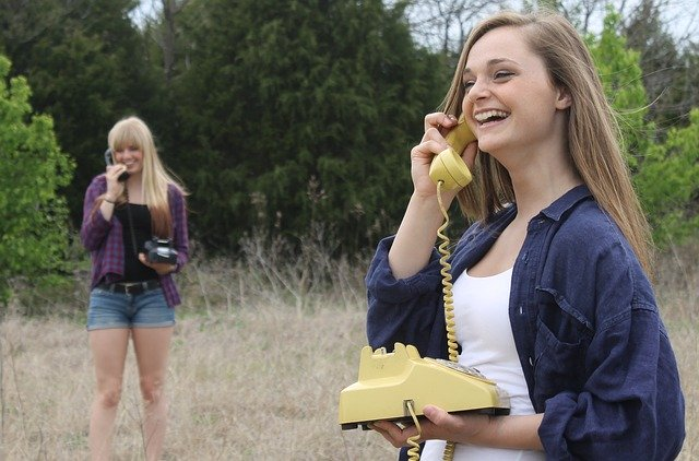 two women stood apart in a field, talking on rotary phones and smiling