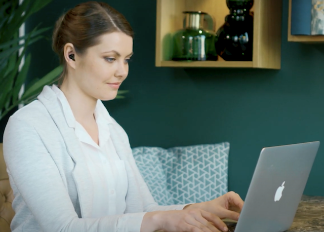 woman wears quieton earbuds while working on laptop