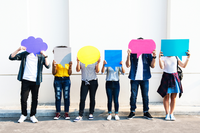 people holding different shaped speech bubble cut-outs