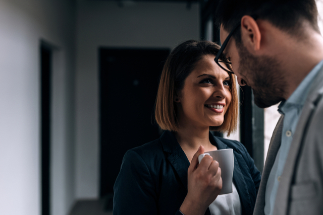 office romance, woman looks at man over a coffee cup