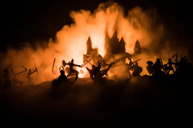 knights silhouetted against fire, shadow of a castle in the background