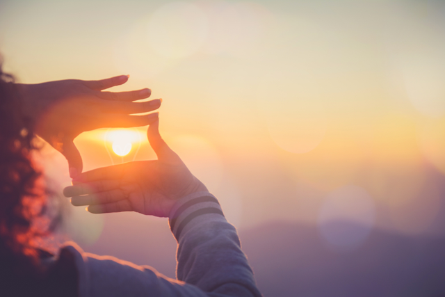 woman frames the setting sun with her hands