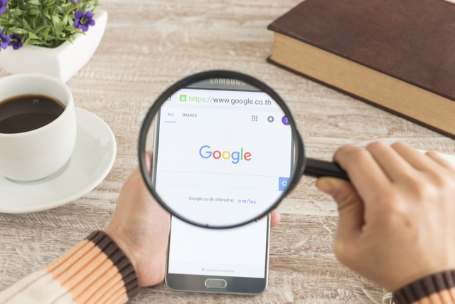 Magnifying glass held over phone displaying search engine