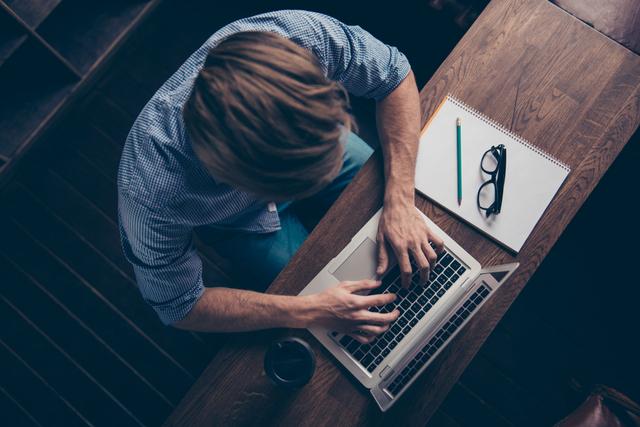 Man sat typing on laptop. Top view shot.
