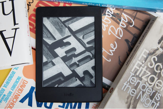 a kindle on a pile of books