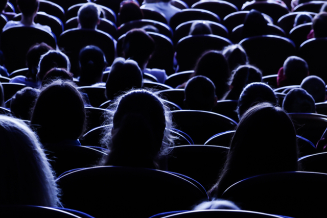 silhouetted cinema audience facing screen (out of shot)