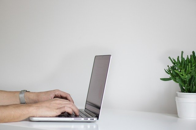 side view of a man's hands typing on a laptop