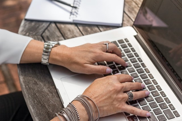 close-up de cima das mãos de uma mulher digitando em um laptop